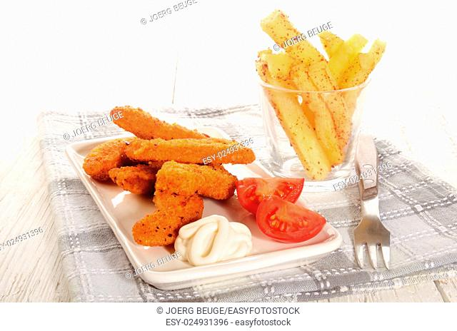 breaded chicken nuggets with mayonnaise, tomato and spicy french fries in a glass