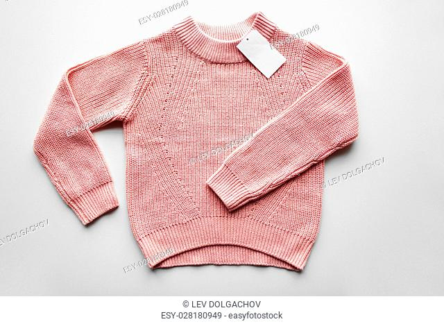 clothes, fashion and objects concept - sweater or pullover with price tag on white background