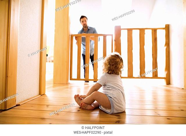 Baby boy sitting on wooden floor looking at father behind barrier at stairs