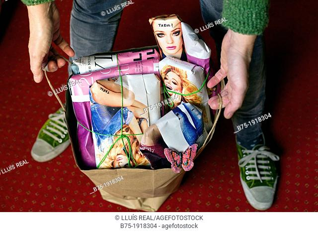 close-up of a young woman showing christmas gifts in a bag