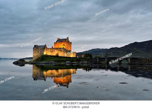 Eilean Donan Castle, ancestral seat of the Scottish clan of Macrae, reflected in Loch Duich in the evening, Dornie, Highlands, Scotland, United Kingdom