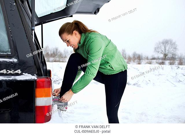 Female jogger tying shoelaces in snow covered scene