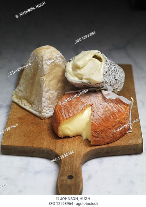 Three soft cheeses on a wooden board