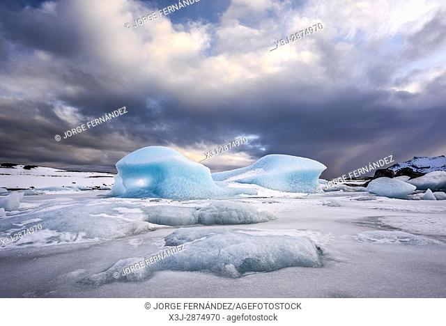 Big piece of blue ice trapped on the ice of the Fjallsarlon glacial lagoon in winter