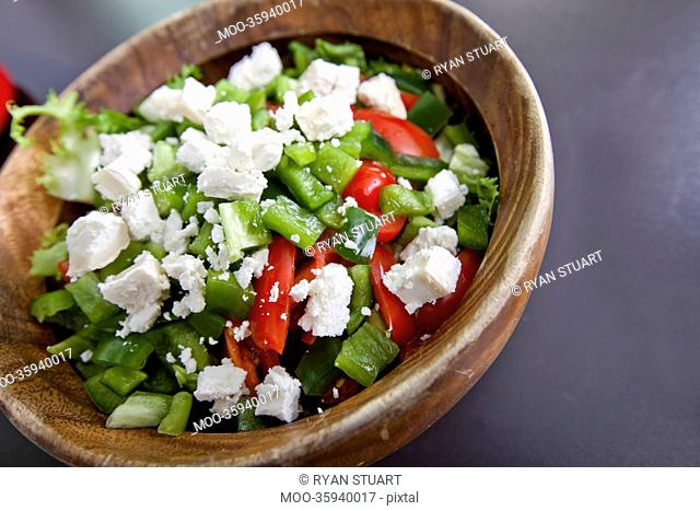 Close-up of vegetable salad in wooden bowl on counter