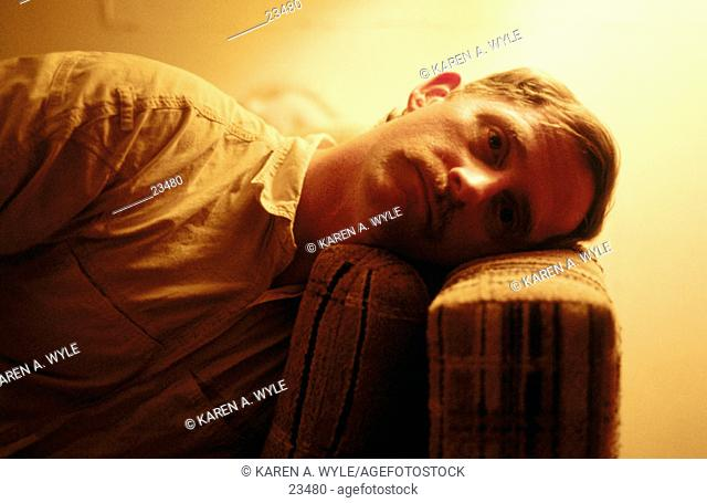 man lying on couch with head on arm of couch, eyes open, stark orange interior lighting