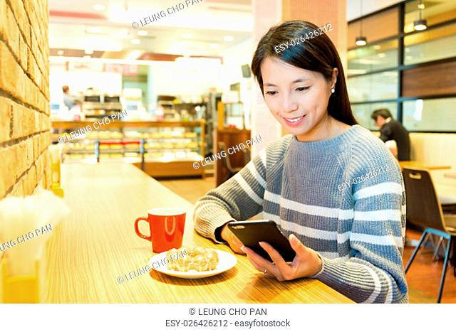 Woman use of cellphone at coffee shop