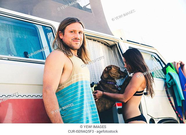 Couple standing beside camper van, pet dog jumping up at woman