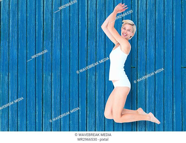 fitness woman jumping with blue wood background