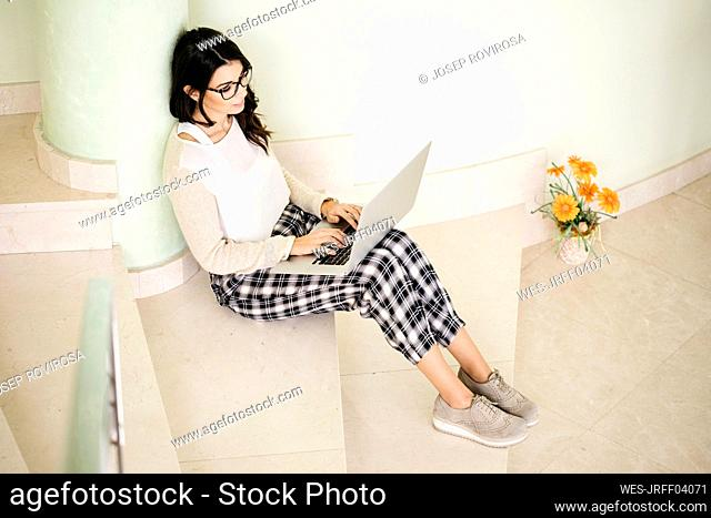 Young woman sitting on stairs using laptop
