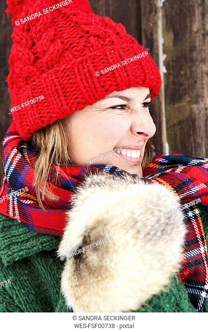 Portrait of woman wearing red bobble hat and fur gloves in winter