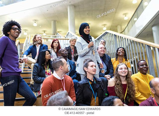 Smiling woman in hijab talking with microphone in conference audience