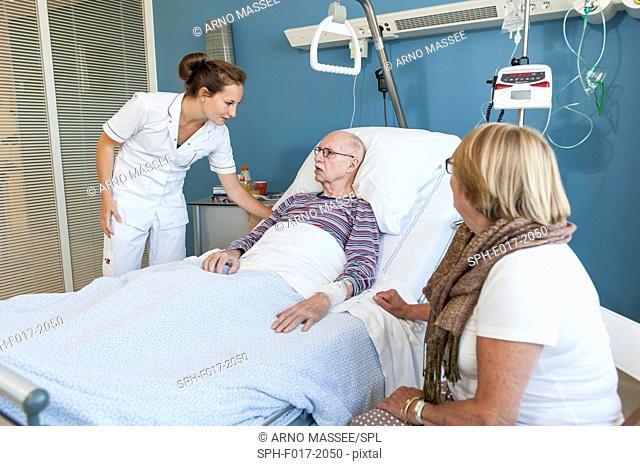 MODEL RELEASED. Nurse talking to senior man in hospital