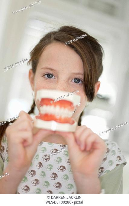Germany, Bavaria, Landsberg, Girl 8-9 holding model of teeth, portrait