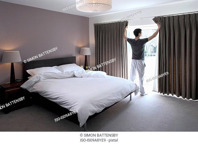 Man looking through glass door of bedroom