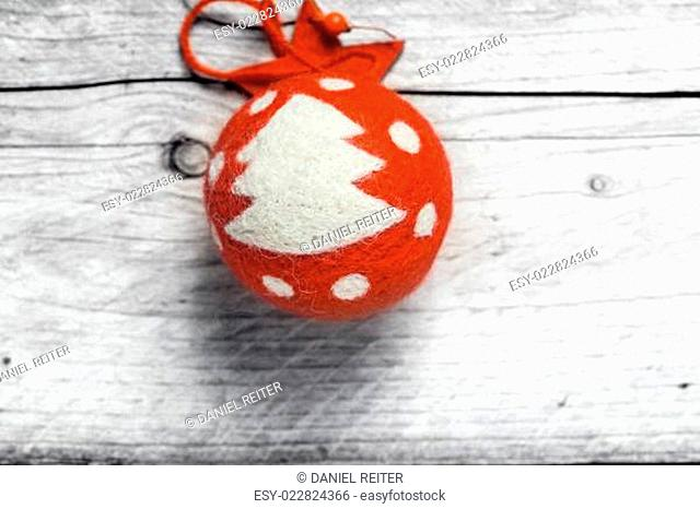 Red Christmas bauble decorated with a tree