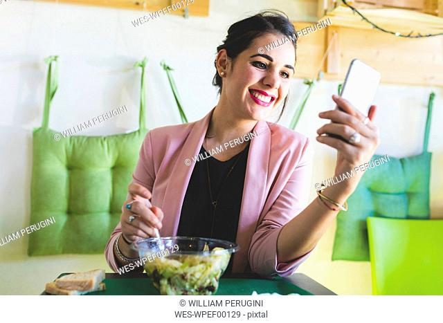 Young businesswoman having healthy lunch and using cell phone
