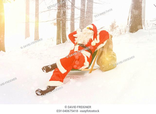 Santa Claus relaxing in a lounger in the woods