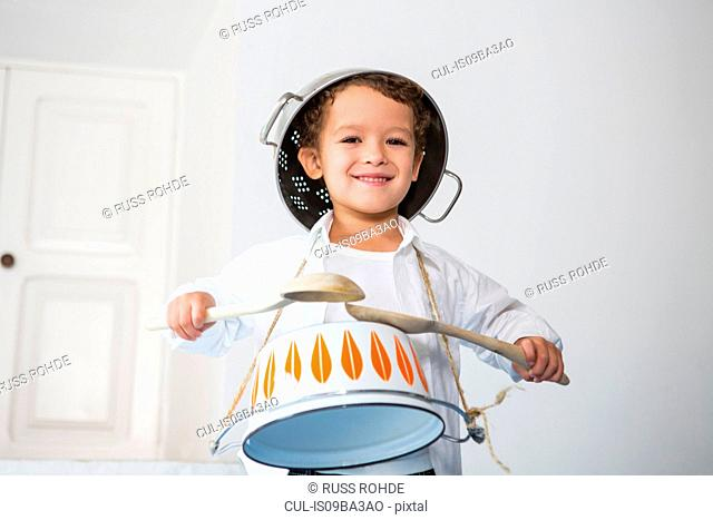 Boy pretending to be drummer using kitchen pots and utensils