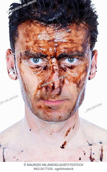 Front view of a man with his face dirty with a brown substance possibly mud