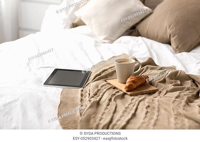 tablet pc, coffee cup and croissant on bed at home