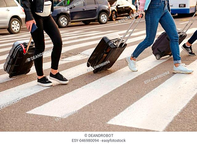 Cropped image of three women walking across pedestrian crossing and carrying luggage after arrival to airport. Air travel or holiday concept