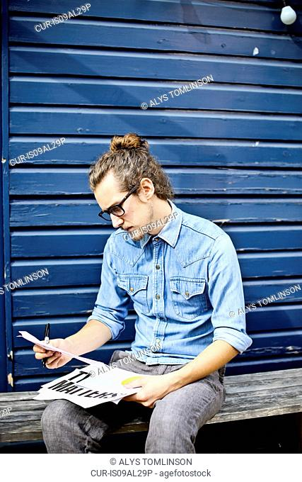 Young man looking at print outs of designs outside
