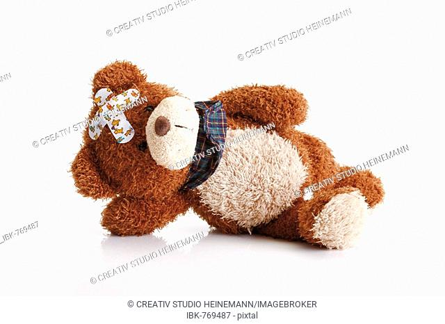 Teddy bear with band-aids on its head laying on floor