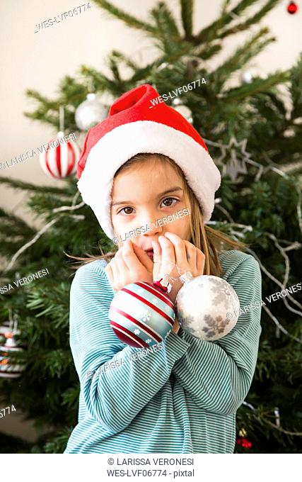 Portrait of little girl with Christmas baubles wearing Christmas cap