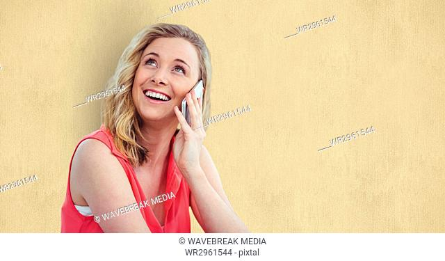 Smiling woman using smart phone over beige background