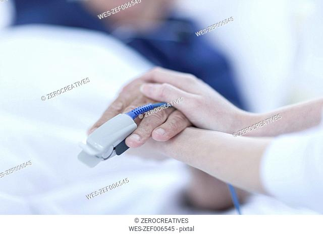 Finger heart monitor on patient, nurse holding hands