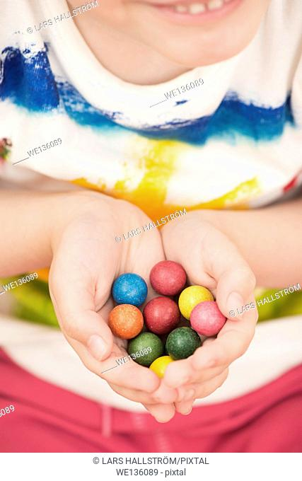 Little girl (5 years) holding colorful toy marbles in her hands. A moment of childhood fun and leisure games