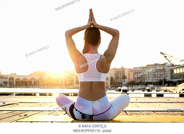 Rear view of Asian woman practicing yoga on a pier at harbour in the evening