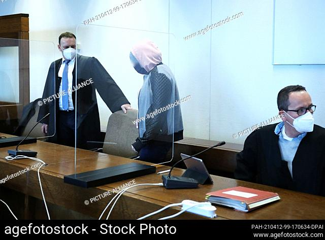 12 April 2021, North Rhine-Westphalia, Cologne: The accused mother (M) walks between lawyers in the courtroom to her seat