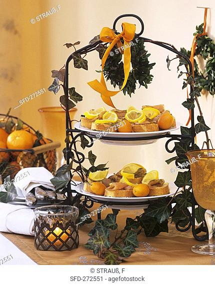Baguette with salmon snacks and kumquats on tiered metal stand