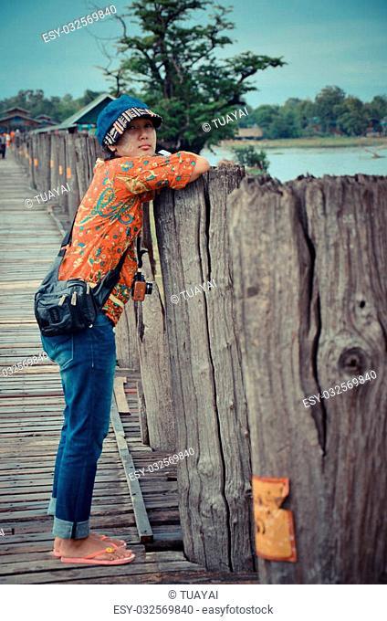 Thai women travel on U Bein Wooden longest Bridge in Amarapura, Myanmar