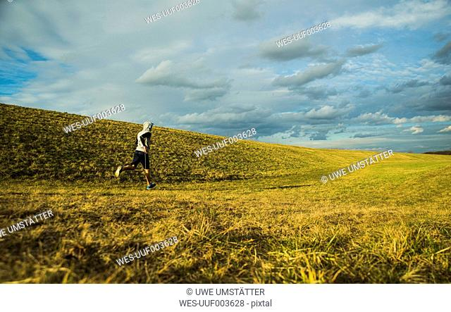 Germany, Mannheim, young man jogging in meadow