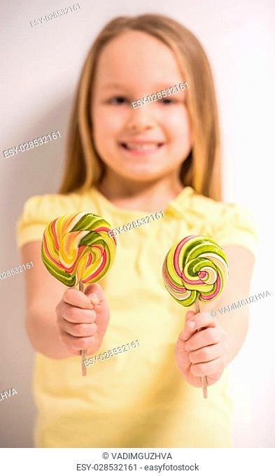Having fun with candies. Cheerful little girl holdong lollipops and smiling. Focus on lollipops