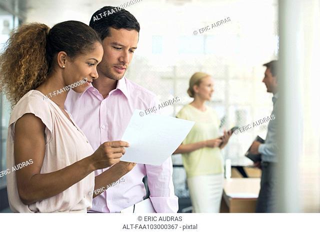 Businesswoman showing colleague document