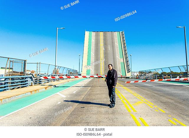 Portrait of worker in front of barrier and drawbridge at biofuel plant