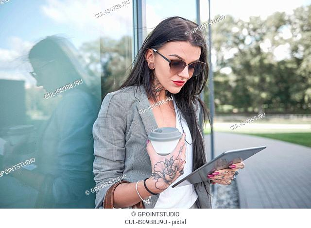 Businesswoman outdoors, holding coffee cup and digital tablet, tattoos on hands