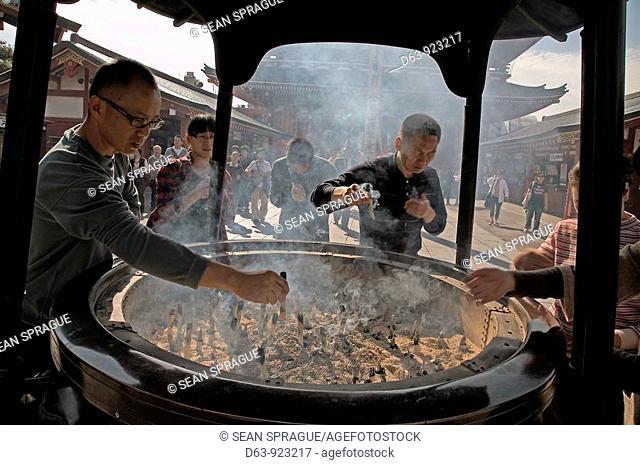 Visitors lighting joss sticks in incense burner, Senso-ji, the Buddhist temple dedicated to Kannon, the Buddhist goddess of Mercy, Asakusa, Tokyo, Japan