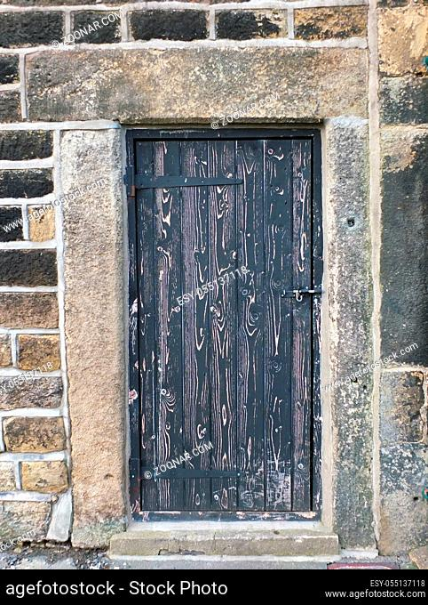 ancient black wooden door with old faded peeling paint in a heavy stone frame with a closed bolt and metal hinges frame