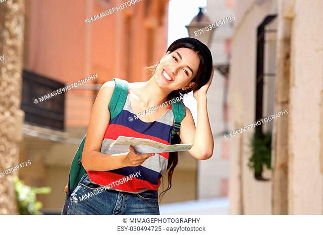 Portrait of a smiling girl on vacation walking in town with bag and map