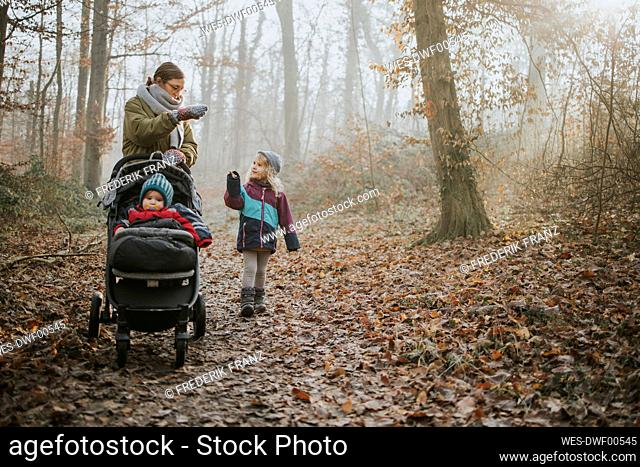 Mother with daughters during forest walk in autumn