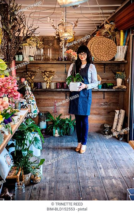 Mixed race florist carrying potted plant in shop
