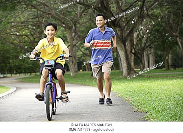 Boy cycling, father running behind him