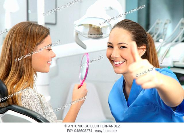 Portrait of a satisfied client and dentist checking dental results at office