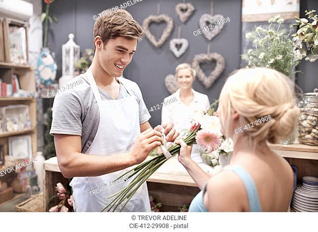Florist tying flowers for woman in flower shop
