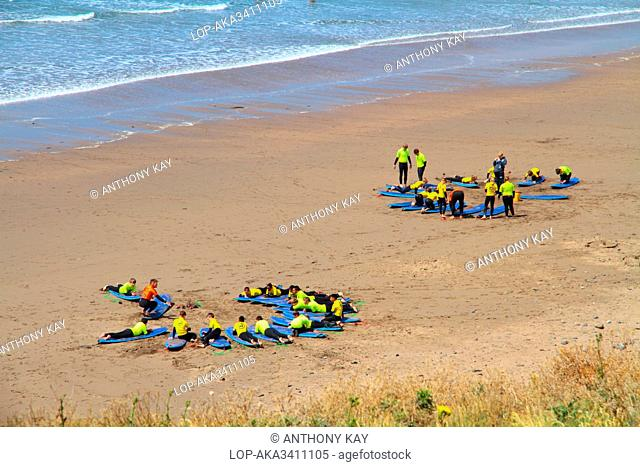 England, Cornwall, Widemouth Bay. Two groups of holiday makers on a sandy beach learning to surf at Widemouth Bay on the north Cornwall coast near Bude